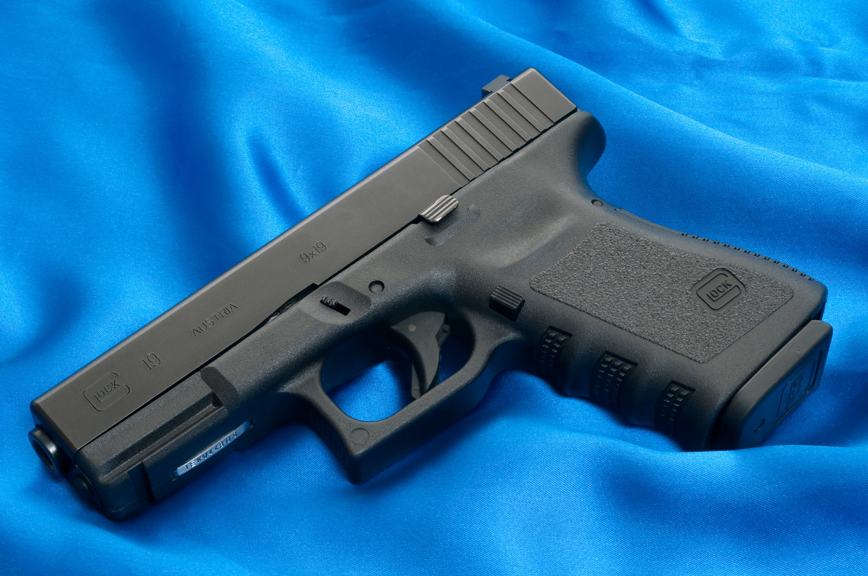 Заряженный пистолет на синем фоне скачать