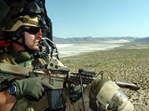 Фотография Солдаты Десант смотрит на пустыню сидя с автоматом в вертолете