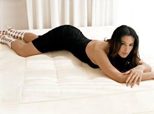 Картинки Моника Беллуччи лежит на кровати в черном платье с вырезом на спину
